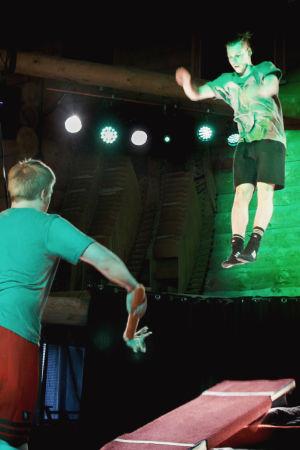 Kaksi sirkustaiteilijaa vipulaudalla, toinen hyppää ilmaan
