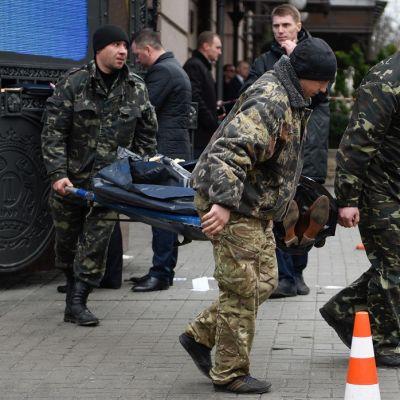 Kolme maastoasuista miestä kantaa paareilla Voronenkovin ruumista. Ruumis on peitetty muovipressulla, kengät näkyvät. Taustalla näkyy kadunvarteen pysäköity musta Mercedes Benz -henkilöauto ja sen takana kulkee poliisin valkopunaista eristysnauhaa.