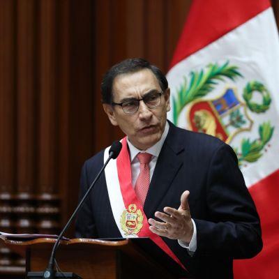 Silmälasipäinen mies puhuu kateederilla, taustalla lippu.