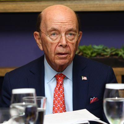 Silmälasipäinen vanha mies, punainen kravatti ja sininen puvun takki, jonka rintapielessä Amerikan lippu -pinssi.
