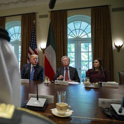 Kaksi miestä ja yksi nainen istuvat pöydän ääressä vasta päätä huivi päistä herraa.