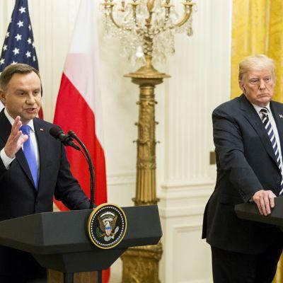 Kaksi miestä seisoo mikrofonien edessä, taustalla Yhdysvaltain ja Puolan liput sekä kristallein koreisteltu lamppu.