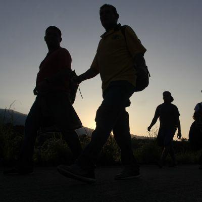 Viisi hahmoa reppujen kanssa kävelee, taustalla pilvetön taivas.
