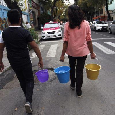 Kaksi ihmistä kantaa vesisankoja.