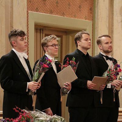 Neljä nuorta miestä seisoo vierekkäin puvut päällä käsissään kukkakimput.