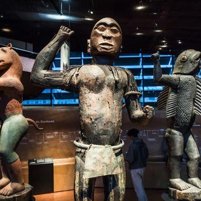 Kolme patsasta, joista yhdellä on kalan vartalo ja ihmisen käden ja jalat.