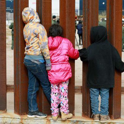 Kolme lasta katselee metallisten tankojen läpi, toisella puolella vihreäasuisia miehiä.