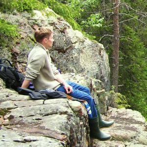 En ung man sitter vid en brant klippa i skogen invid en liten älv.