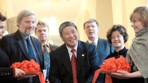 Kinesiska ambassadören (kvinna), direktören för institutet, representant från Renmin, klipper bandet vid invigning, fler personer runt omkring.
