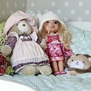 En bäddad säng med en docka, en nalle och ett mjukt lejon placerade på mitten på ett harmoniskt sätt.