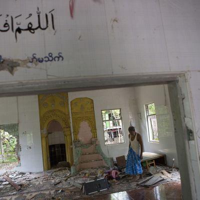 Mies katselee tuhonjälkiä moskeijassa, jossa on muun muassa ikkunat rikottu ja seinään tehty reikiä.
