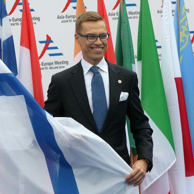 Pääministeri Alexander Stubb seisoo lippujen kanssa