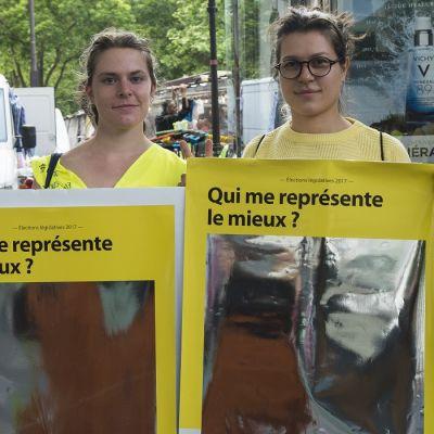 """Kaksi naista pitää edessään keltaisia julisteita joissa lukee """"qui me représente le mieux ?"""""""