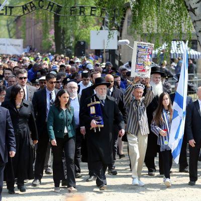 """Ihmisjoukko alittaa portin, jossa lukee """"Arbeit macht frei"""". Kaksi kantaa Israelin lippua, rabbi juutalaista kirjakääröä."""