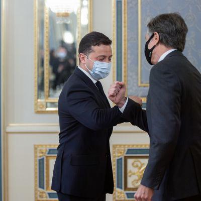 Miehet tervehtivät toisiaan maskit kasvoilla kyynärpäätervehdyksellä.