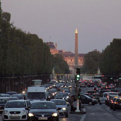 Autoja Pariisin liikenteessä iltahämärässä.