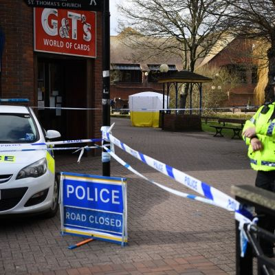 """Keltaiseen huomioliiviin pukeutunut brittipoliisi seisoo vartiossa poliisin nauhalla eristetyn alueen laidalla kuvan oikealla reunalla. Kuvan  vasemmalla puolella on poliisiauto parkkeerattuna. Auton vieressä on maassa kyltti, jossa lukee valkoisin kirjaimin sinisellä pohjalla: """"Poliisi. Tie suljettu."""" Taustalla näkyy valko-keltainen teltta, jolla on peitetty yksi puiston penkeistä."""