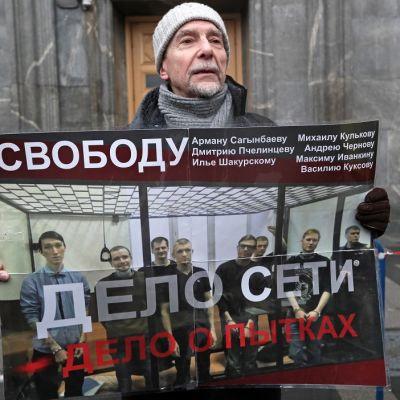 Kuvassa mies, joka pitää käsisään julistetta, jossa on tuomittujen kuvat.