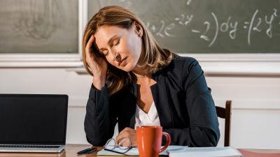 Trött kvinnlig lärare i klassrum