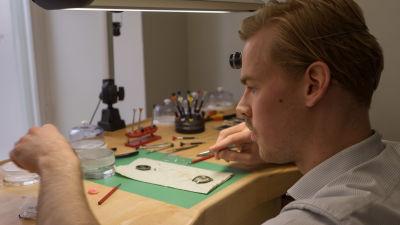 Urmakare Eric Wikman putsar en gammal klocka