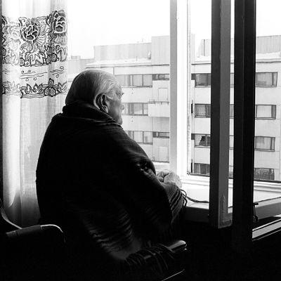 Vanha nainen katselee ikkunasta ulos.