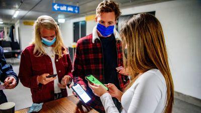 Några personer i munskydd visar telefon med coronapass på en klubb.