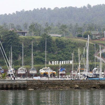 Kuva Samalin satamasta. Vedessä purjeveneitä, taustalla Ocean View resort ja viidakkoa.