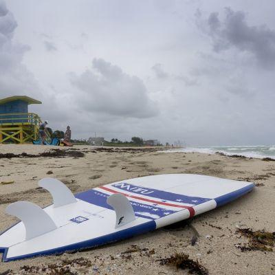Yksinäinen surffilauta lojuu rannalla, jonka taivaalla on tummia pilviä.