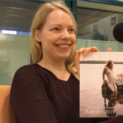 Nainen näyttää kädessä olevaa valokuvaa