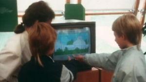 Barn trycker på en dators pekskärm, 1986