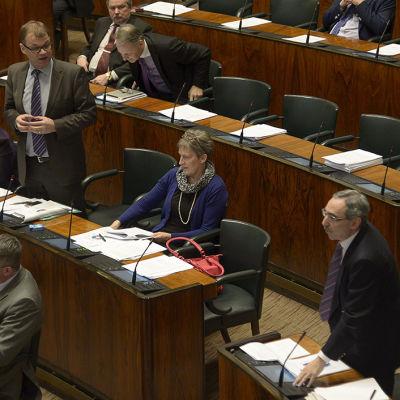 Riksdagsledamöter diskuterar oppositionens interpellation om barnbidragen.
