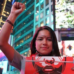 Helena Sirén Gualinga osoittaa mieltään alkuperäiskansojen puolesta. Oikea käsi kohotettuna, vasen pitelee kylttiä. Taustalla kaupunkimaisema.