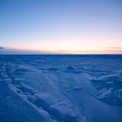Iso jäälautta ja laiva, taustalla Aurinko hieman horisontin yläpuolella.