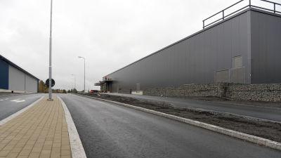 En grå lång och hög vägg invid en väg.