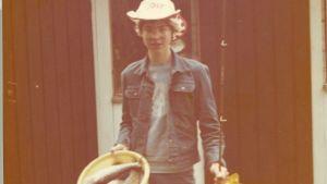 En ung Ben Granfelt med fatet fullt med fisk och ett kastspö i handen