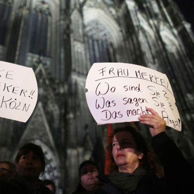 """Kaksi naista pitelee saksankielisiä kylttejä. Toisessa lukee: """"Kiitos, rouva Reker. Köln-parka."""" Toisen teksti kuuluu: """"Rouva Merkel. Missä olette? Mitä sanotte? Tämä pelottaa."""" Naisten taustalla on Kölnin katedraali."""