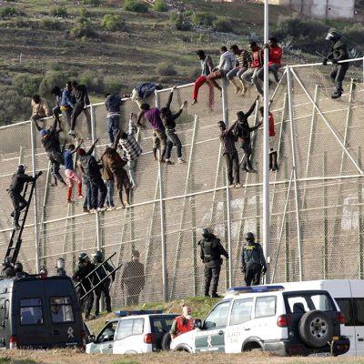 Pakolaiset yrittivät kiivetä raja-aidan yli Melillassa 15. lokakuuta 2014.