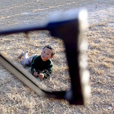 Lapsi aseen takatuen lävitse nähtynyä.