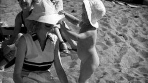 Nainen ja lapsi rannalla.