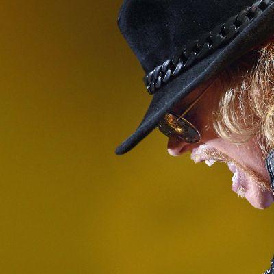 Axl Rose mustalierisessä hatussaan keltaisenoranssia taustaa vasten.