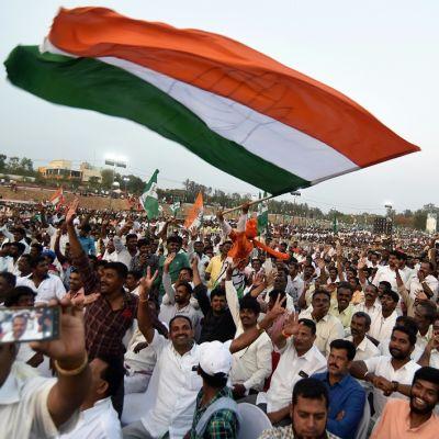 Kuvassa kongressipuolueen kannattajia. Kuvan ylälaidassa suuri Intian lippu, jota yksi kampanjatilaisuuden osallistujista heiluttaa.