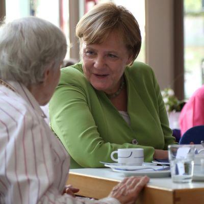 Vihreäjakkuinen nainen keskustele harmaahiuksisen naisen kanssa.