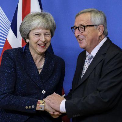 Hymyilyvä nainen ja mies kättelevät, taustalla Britannian lippuja EU-komissio merkki.