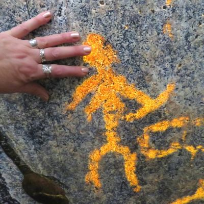 Käsi kalliomaalauksen ihmishahmoa vasten