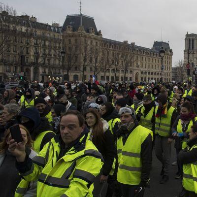 Keltaisiin huomioliiveihin pukeutuneet mielenosoittajat marssivat kadulla. Taustalla näkyy Notre Damen katedraali.