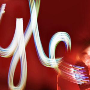 Käsi heilauttaa kännykkää ja valoviiruista muodostuu sana Yle.