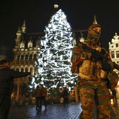 Aseistautunut maastopukuinen sotilas partioi valaistun joulukuusen edessä.