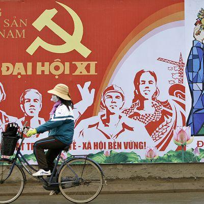 Nainen pyöräilee sosialistiseinämaalauksen edessä.