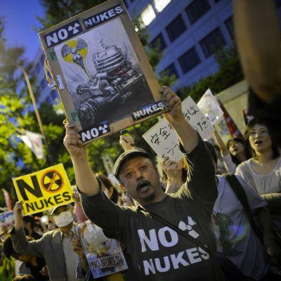 Mielenosoittajat pitelevät ydinvoimaa vastustavia kylttejä yläpuolellaan.