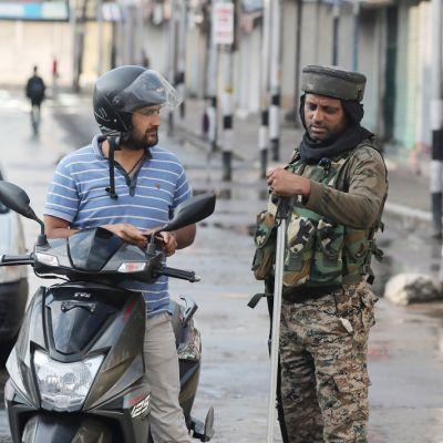 Kuvassa sotilas tarkastaa skootterin selässä istuvan miehen henkilöllisyyspapereita.